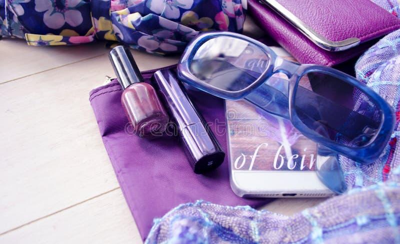 时兴的女性辅助部件观看太阳镜唇膏紫罗兰色传动器和手机 辅助部件背景秀丽生活红色仍然s事情白人妇女 免版税库存照片