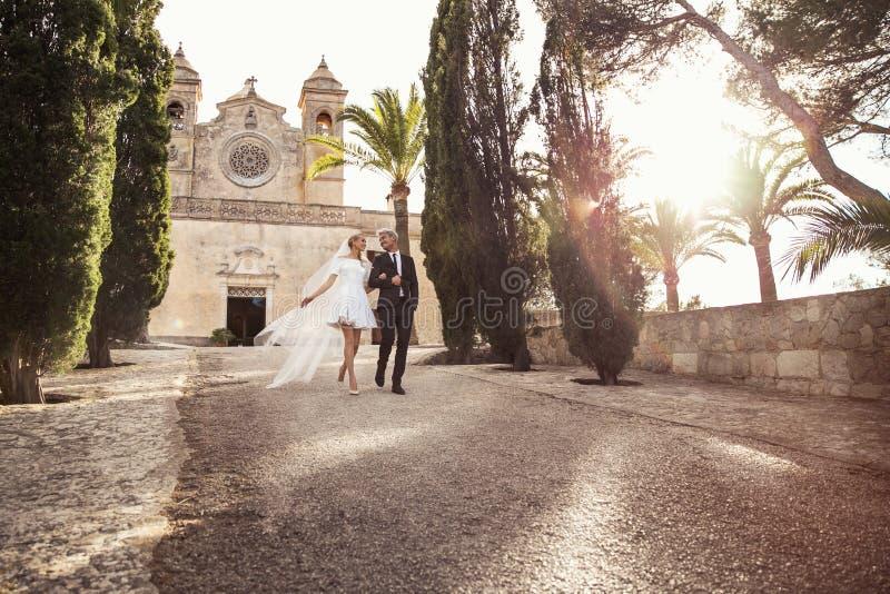 时兴的婚礼夫妇临近天主教会 新娘仪式教会新郎婚礼 室外纵向 库存图片