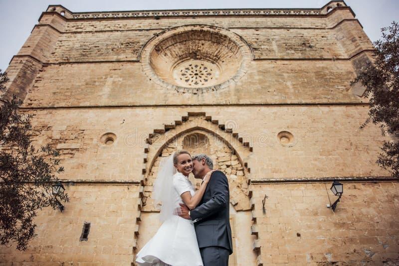 时兴的婚礼夫妇临近天主教会 新娘仪式教会新郎婚礼 室外纵向 免版税图库摄影