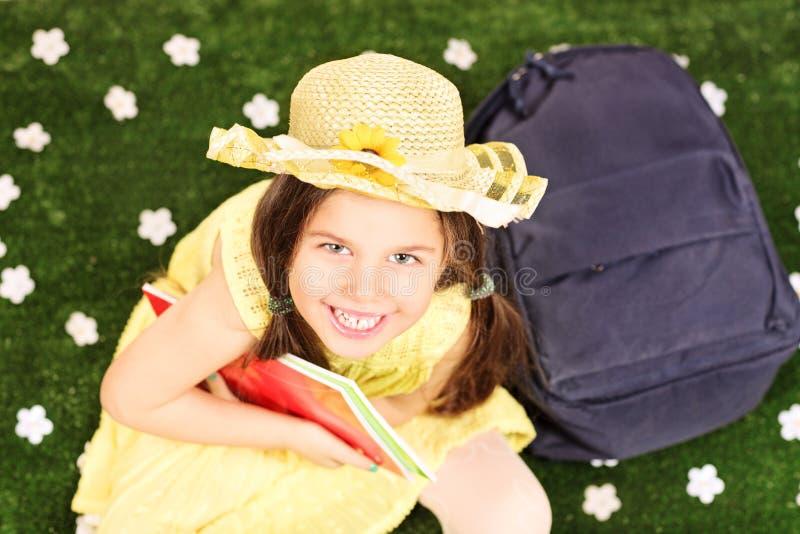 时兴的小女孩坐与笔记本和后面的草 库存照片