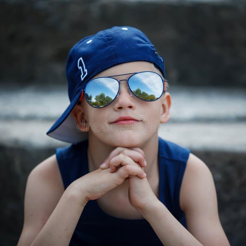 时兴的小男孩画象太阳镜和盖帽的 童年 免版税库存照片