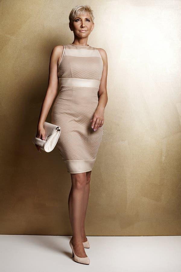 时兴的礼服的典雅的白肤金发的妇女 图库摄影