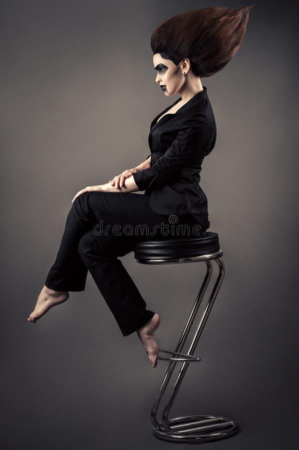 时兴的美丽的女商人坐与豪华的头发和黑暗的构成的高凳 免版税库存照片