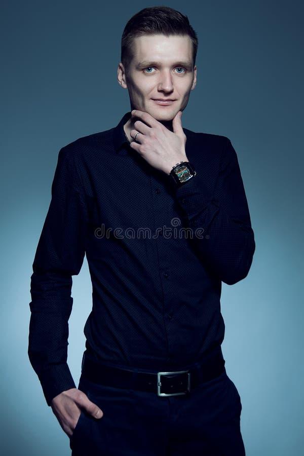 时兴的英俊的人画象摆在ov的一件黑衬衣的 库存照片