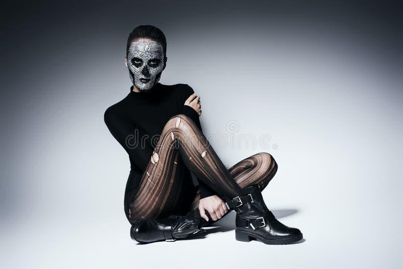 时兴的黑暗的妇女坐地板 库存照片