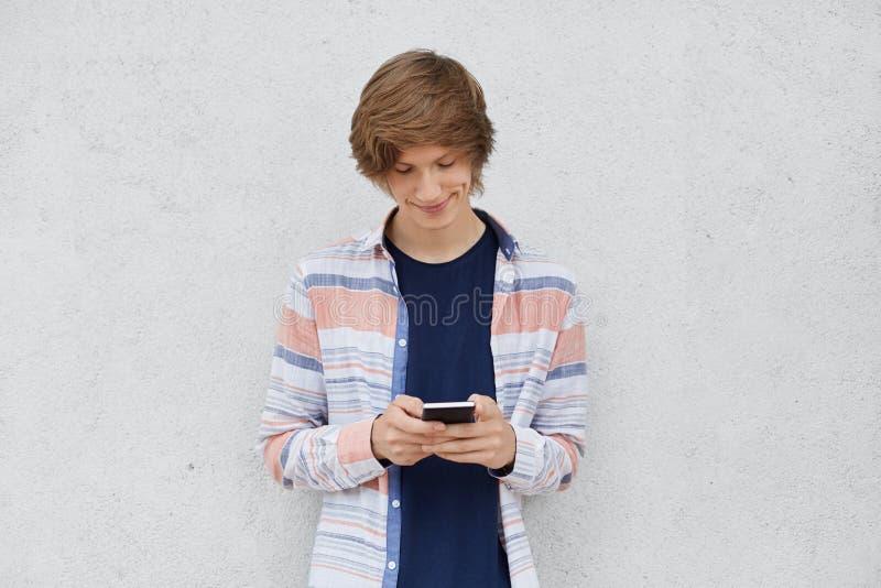 时兴的十几岁的男孩佩带的衬衣,固定的单元电话在手,与朋友的传讯或在网上使用比赛上使用自由inte 免版税库存照片