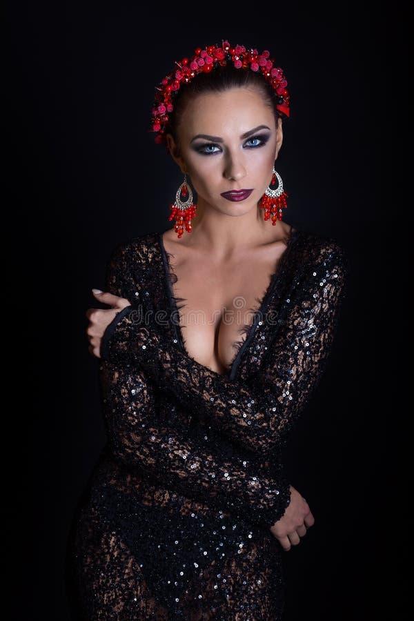 昂贵的首饰花圈耳环和圆环在一个美丽的性感的典雅的深色的女孩与一个明亮的晚上在甚而黑色化妆 图库摄影