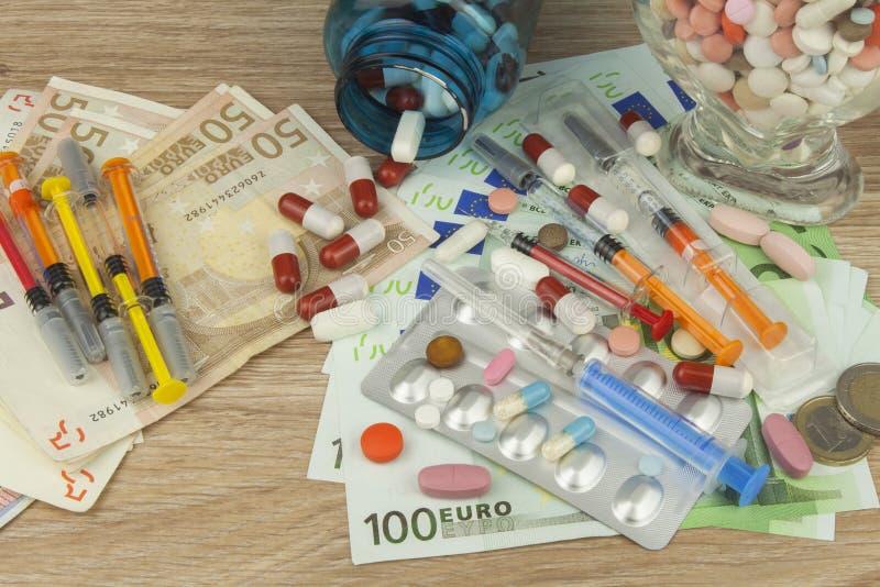 昂贵的治疗的金钱 货币和药片 不同的颜色药片在金钱的 库存图片