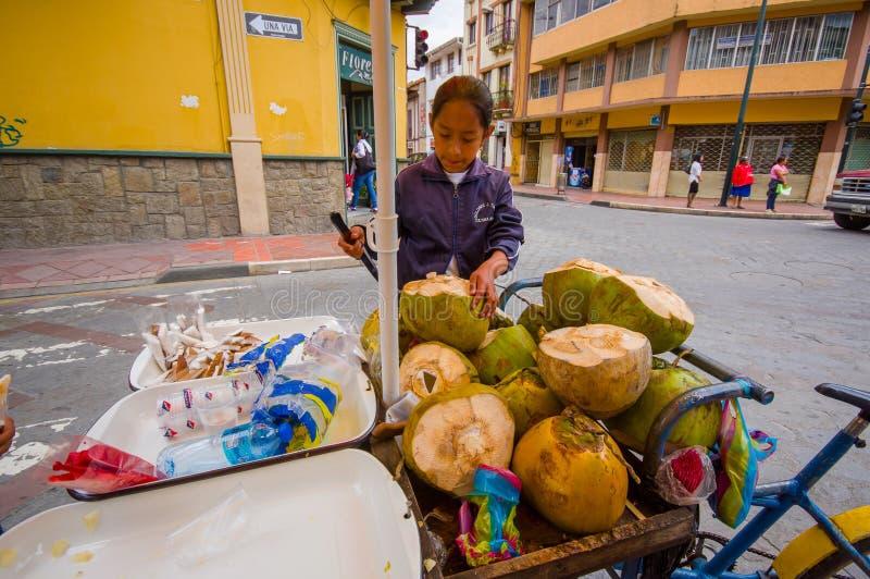 昆卡省,厄瓜多尔- 2015年4月22日:工作在椰子自行车商店的年轻十几岁的女孩在市中心,拿着刀子使用它对wor 免版税库存照片