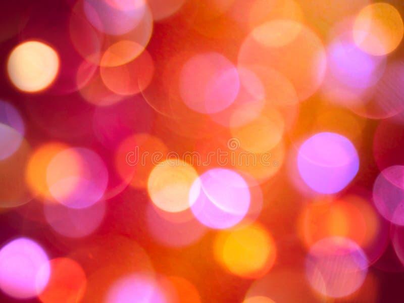 明亮发光橙色和紫色发光的被弄脏的光抽象庆祝背景 免版税库存照片