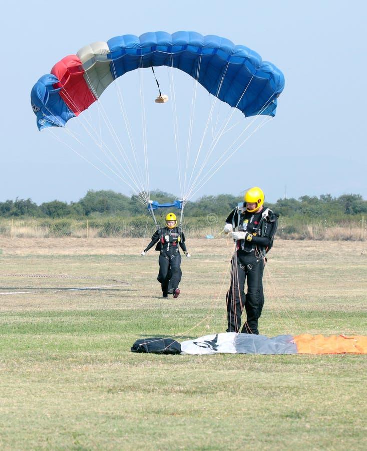 明亮地做安全着陆的女性跳伞运动员在草以开放 免版税库存图片