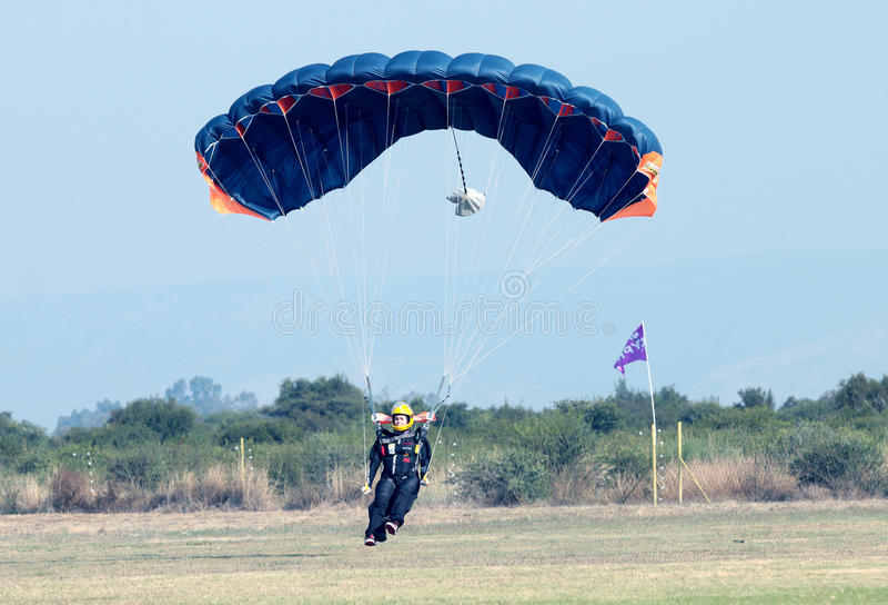 明亮地做安全着陆的女性跳伞运动员在草以开放 免版税图库摄影