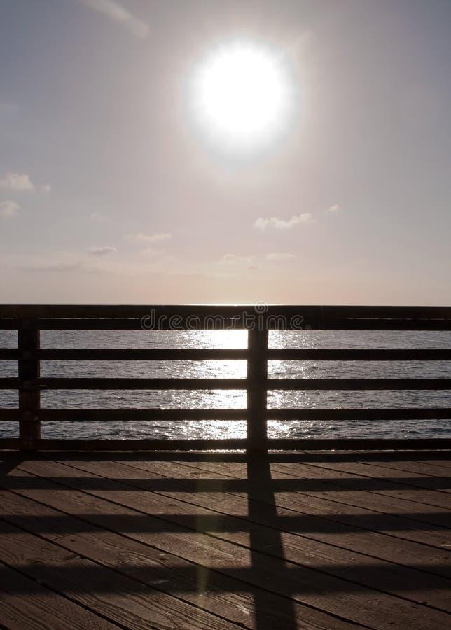 明亮地发光在太平洋的太阳被看见通过在码头的木栏杆 免版税库存图片