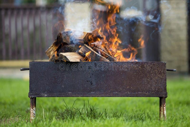 明亮地烧在金属烤肉的箱子木柴室外 凸轮 免版税库存照片