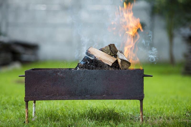 明亮地烧在金属烤肉的箱子木柴室外 凸轮 免版税图库摄影
