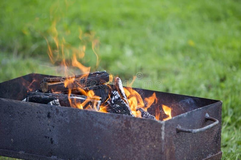 明亮地烧在金属烤肉的箱子木柴室外 野营,安全和旅游业概念 图库摄影