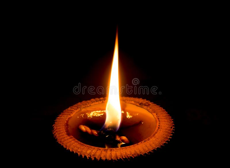 明亮地烧在黑背景中的轻的蜡烛 在瓦器盘子的蜡烛光 库存照片