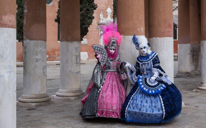 明亮地色的桃红色和蓝色服装的被掩没的妇女在威尼斯狂欢节 免版税图库摄影