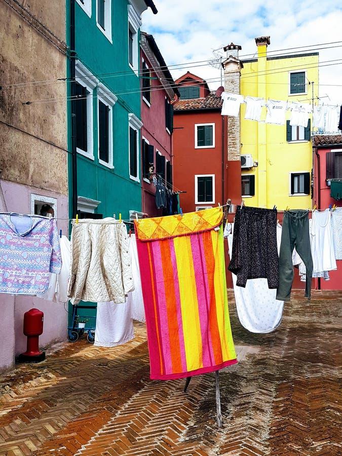 明亮地色的洗衣店横跨在burano前面威尼斯意大利的明亮地色的家的街道垂悬 免版税库存照片