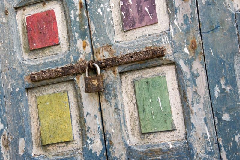 明亮地色的片状被绘的老窗口快门巩固了与一个生锈的螺栓并且挂锁荷兰掀动 免版税库存图片