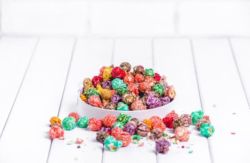 明亮地色的糖煮的玉米花,白色背景 速食,在浅粉红色的碗的水果味道的玉米花的水平的图象 colo 库存图片