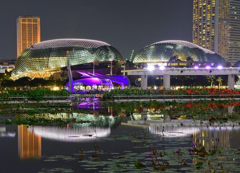 明亮地被点燃的广场剧院的夜风景海湾的在小游艇船坞海湾新加坡 图库摄影