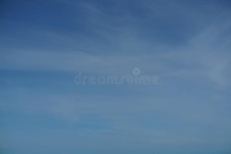 明亮的与轻的白色云彩的梯度蓝天看法在海洋上 免版税库存照片