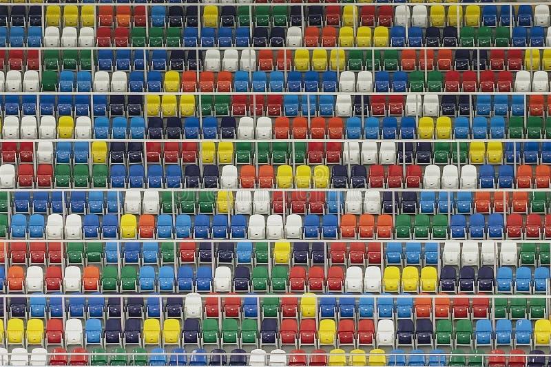 明亮的五颜六色的塑料位子,正面看台体育场许多行,背景的 免版税库存照片