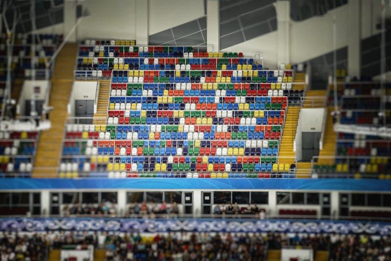 明亮的五颜六色的塑料位子,正面看台体育场许多行  免版税库存照片