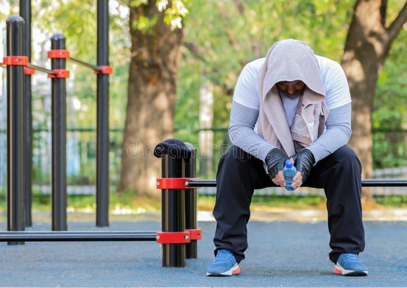 明亮的体育衣裳的一个年轻人有在他的头的一块毛巾和一个瓶的水在他的手上坐健身房公开 免版税库存图片