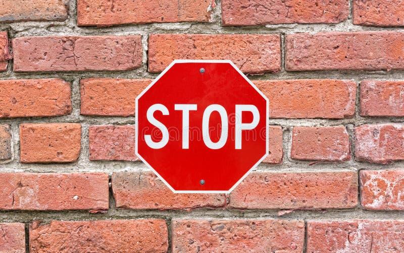 明亮的停车牌附有了大砖房屋板壁 免版税库存照片