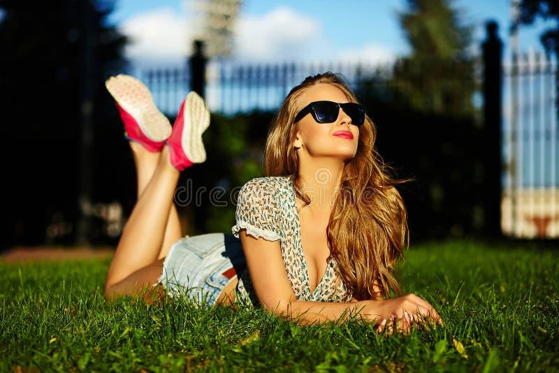 明亮的偶然布料的时髦的微笑的女孩在牛仔裤短缺户外 免版税库存照片