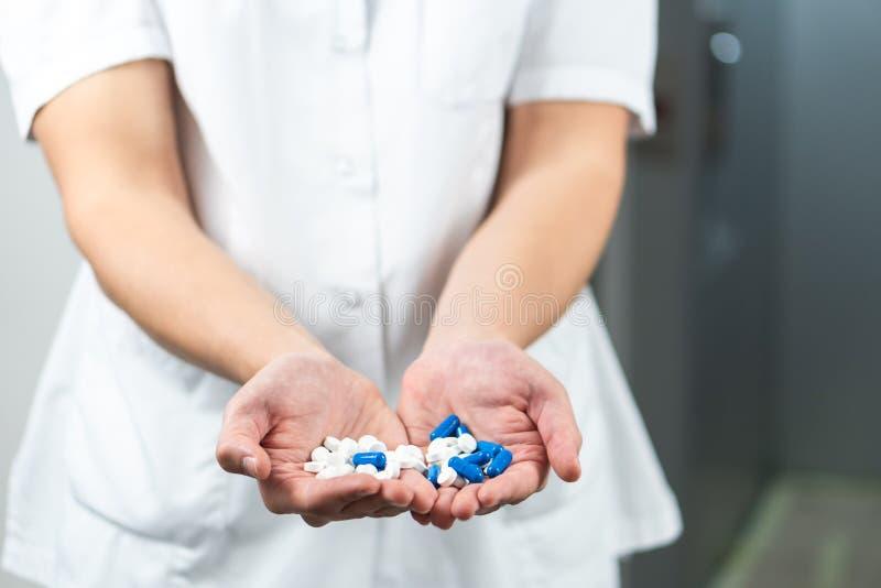 明亮的关闭制服的男性医生有听诊器和在手上拿着的蓝色和白色药片 库存图片