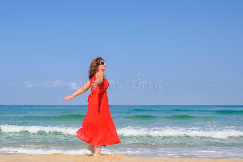 明亮的典雅的红色礼服的美丽的夫人在海滩 库存照片
