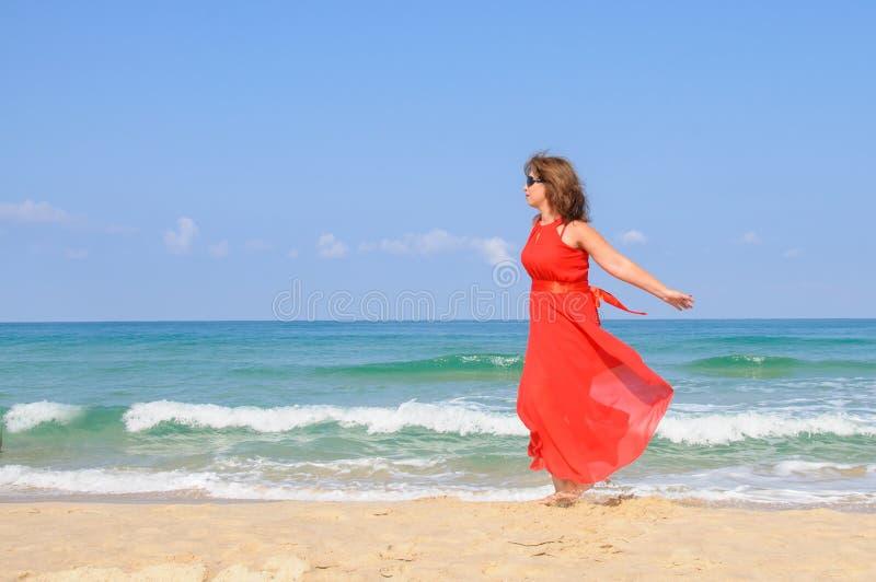 明亮的典雅的红色礼服的美丽的夫人在海滩 库存图片