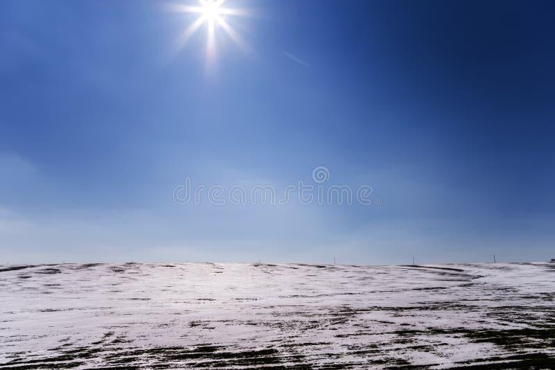 明亮的冬天太阳发光在与电杆线的冰冷的小山  免版税图库摄影