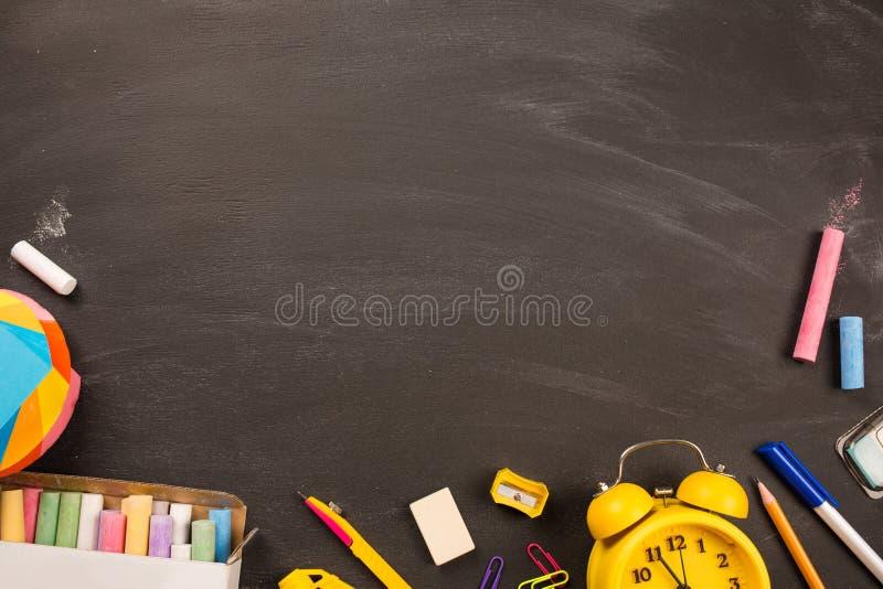 明亮的办公用品,在黑黑板顶视图,拷贝空间的黄色闹钟 概念:回到学校 库存图片