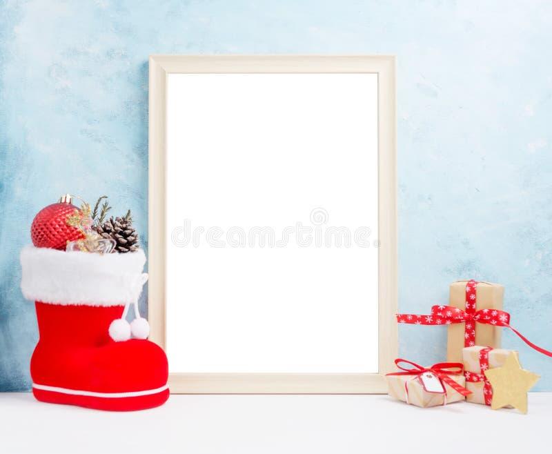 明亮的圣诞节嘲笑与大照片框架:欢乐礼物盒、玩具和冷杉锥体在红色圣诞老人` s解雇新年概念 免版税库存图片