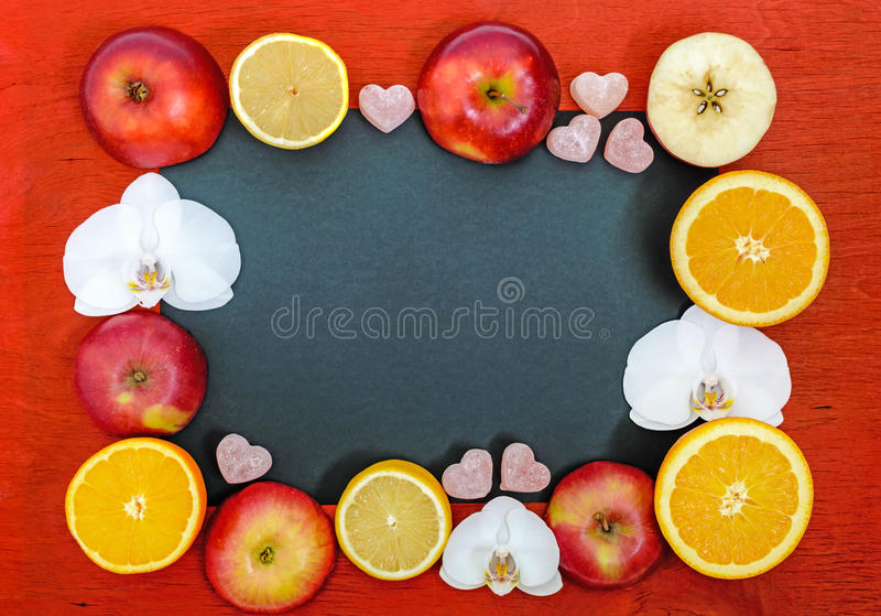 明亮的多彩多姿的背景框架用柑橘柠檬,桔子,切苹果,果冻甜点以心脏的形式 免版税图库摄影