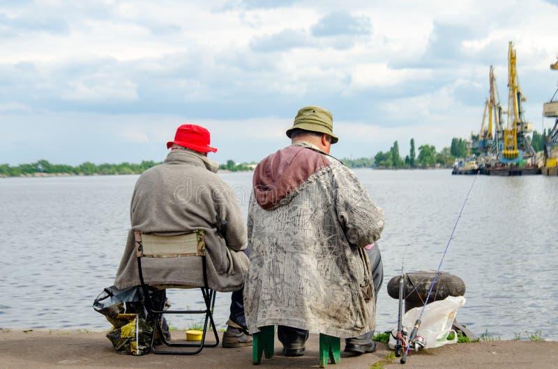 明亮的帽子的渔夫在河的河岸 图库摄影