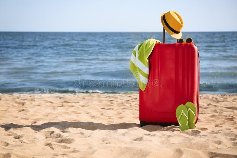 明亮的手提箱和不同的海滩辅助部件在沙子在海附近 免版税图库摄影