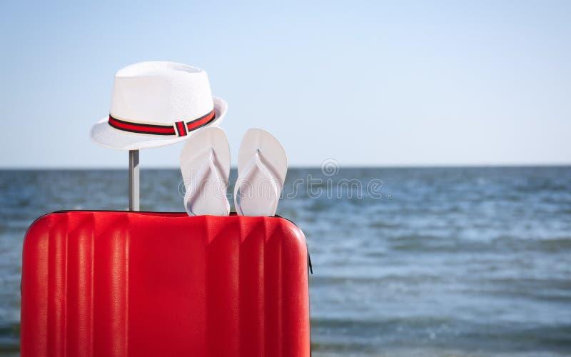 明亮的手提箱和不同的海滩辅助部件在沙子在海附近 库存照片