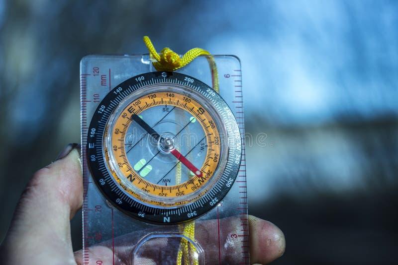 明亮的指南针在一个旅客的手上在自然被弄脏的背景的晚上  库存照片