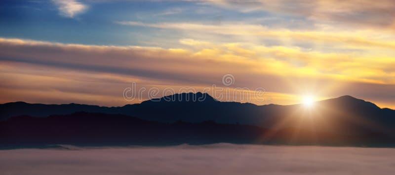 明亮的日出,在山谷的薄雾 免版税库存照片