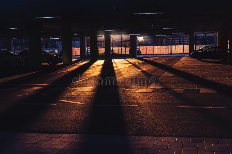 明亮的橙色日落和长的阴影与有些汽车在距离停放了 库存图片