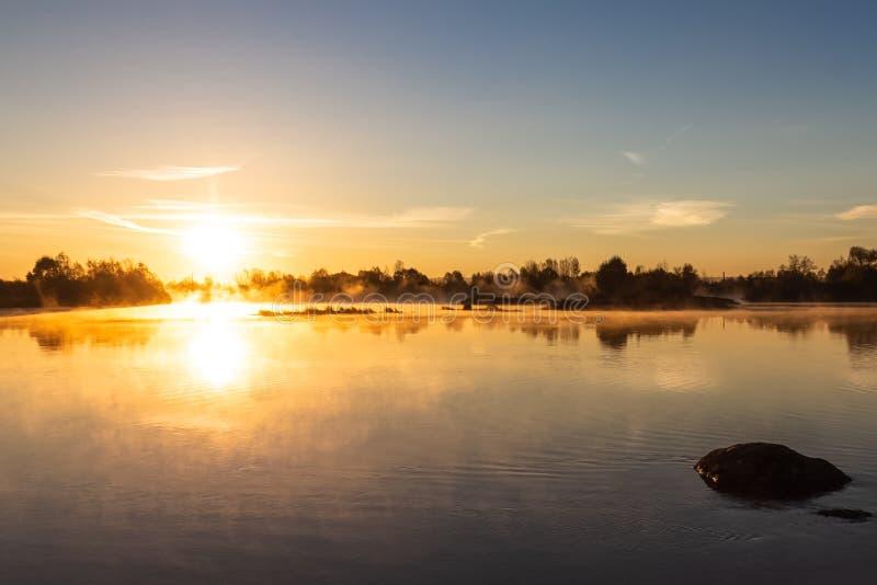 明亮的橙色黎明温暖的光芒打消在一条镇静河的薄雾, illu 库存图片