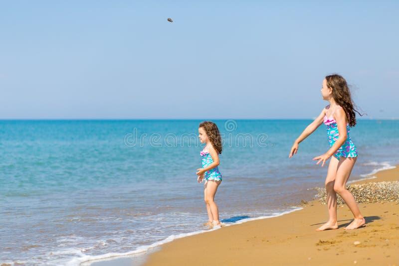 明亮的泳装的女孩在海滩使用 孩子在度假 r 愉快的姐妹 库存照片