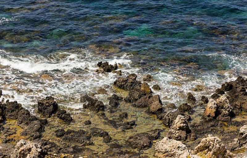 明亮的清楚的大海海石火山的岸泡沫 库存照片