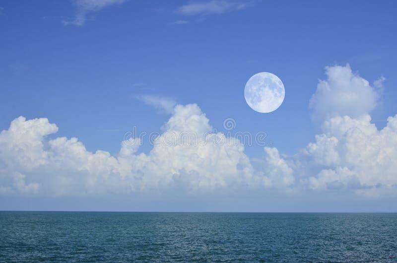 明亮的白色云彩和月亮在蓝天在绿浪 免版税库存照片