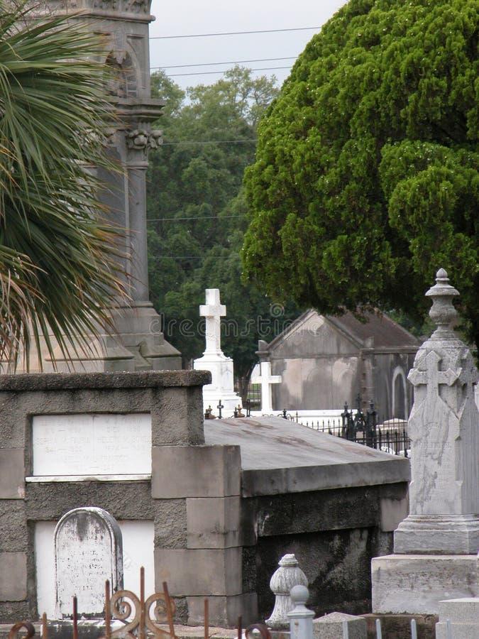 明亮的白色十字架在老公墓背景中  免版税库存照片